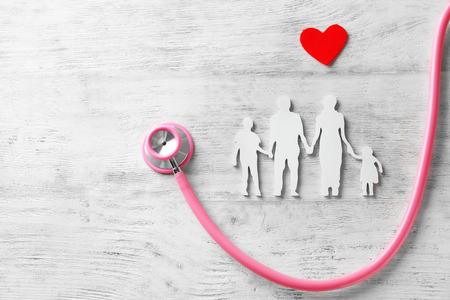 Familie figuur, rood hart en stethoscoop op houten achtergrond. Zorgconcept Stockfoto