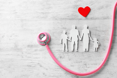 Figura di famiglia, cuore rosso e stetoscopio su fondo di legno. Concetto di assistenza sanitaria Archivio Fotografico