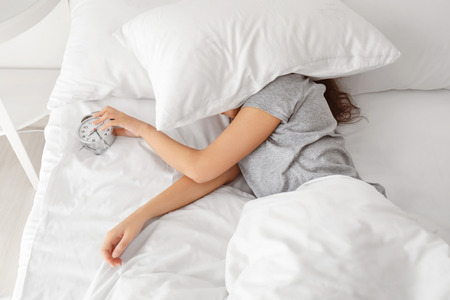 Morning of young woman sleeping with alarm clock in bed