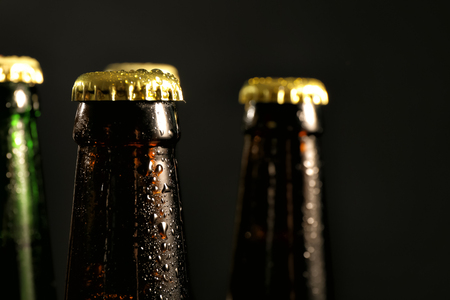 Glass bottles of cold beer on dark background, closeup