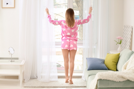 Beautiful young woman opening curtains in morning Imagens