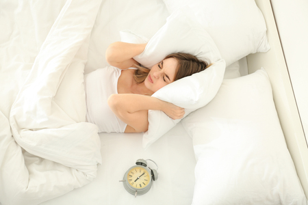 Alarming clock and irritated woman covering her ears with pillow in bed. Morning time Фото со стока
