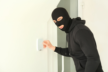 Male thief breaking security system indoors