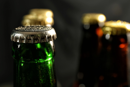 Glass bottle of cold beer on dark background, closeup
