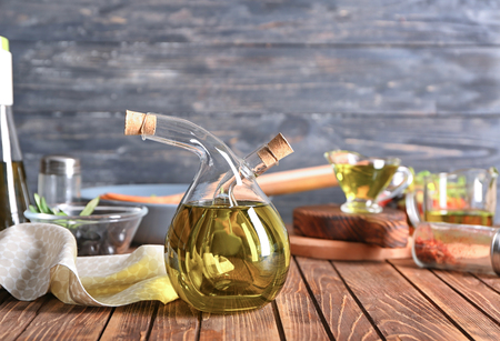 Bottle with olive oil on wooden table 스톡 콘텐츠