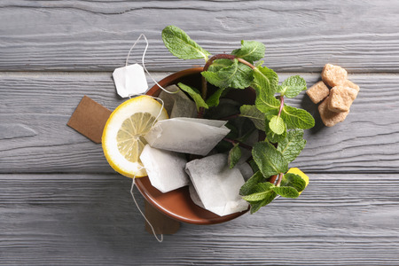 Bowl with tea bags and mint on wooden table Standard-Bild
