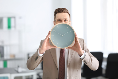 Successful businessman with clock in office. Time management concept Stockfoto