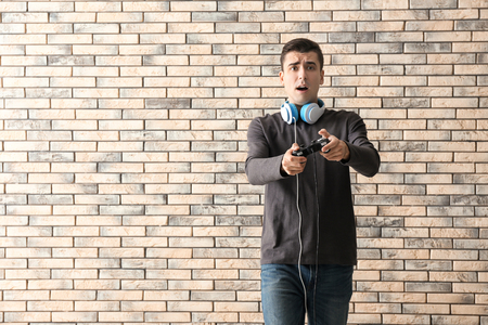 Young man with gamepad on brick wall background Standard-Bild