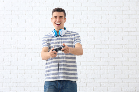Young man with gamepad on brick wall background Banque d'images