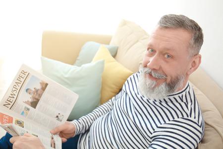 Senior man reading newspaper at home 版權商用圖片
