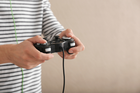 Young man with gamepad on color background Banque d'images
