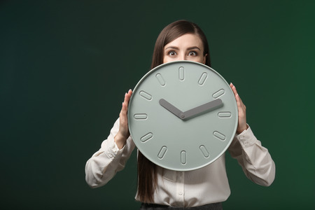 Woman with clock on color background. Time management concept
