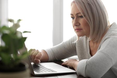 Mujer madura leyendo noticias en la pantalla de un portátil en el café