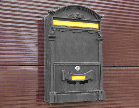 Vintage mailbox on metal fence outdoors