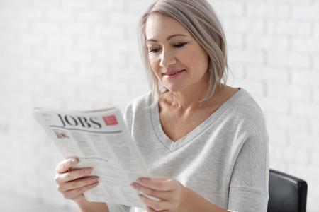 Mature woman reading newspaper on blurred background 版權商用圖片
