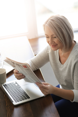 Mature woman reading newspaper in cafe
