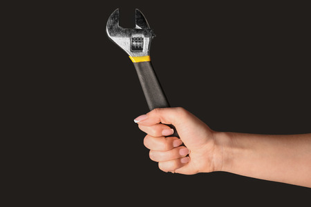 Hand of female car mechanic with adjustable wrench on black background Imagens