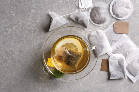 Brewing of hot tea in glass cup on table