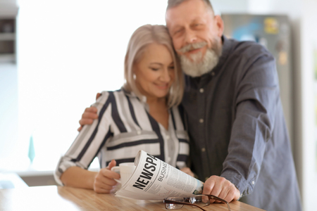 Mature couple reading newspaper at home