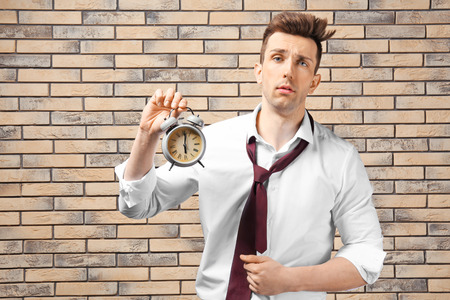 Troubled businessman with alarm clock against brick wall. Time management concept