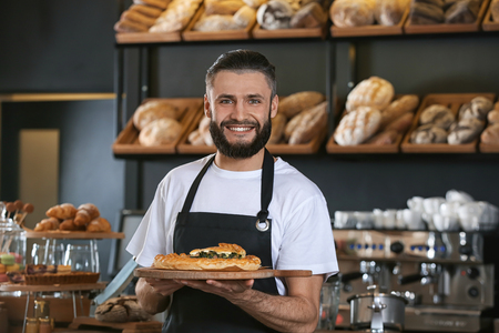 Male baker holding wooden board with delicious pie indoors