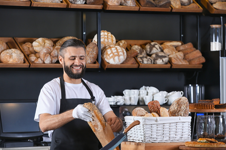 Young man packaging bread for customer in bakery Banco de Imagens