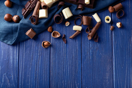 Chocolate curls with hazelnuts on color wooden background