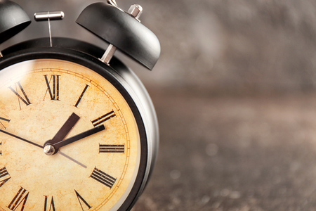 Alarm clock on grey background, closeup. Time management concept 免版税图像