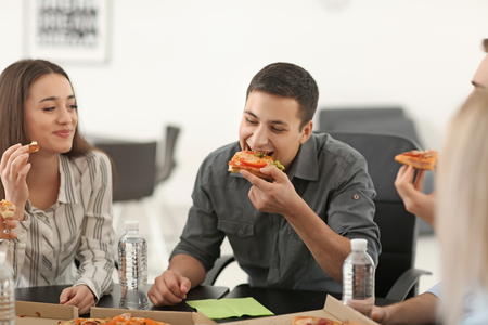 Young people eating pizza at table in office