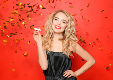 Portrait of beautiful young woman with party whistle and falling confetti on color background 写真素材