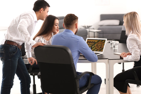 Young people using laptop for ordering food in office Stock Photo