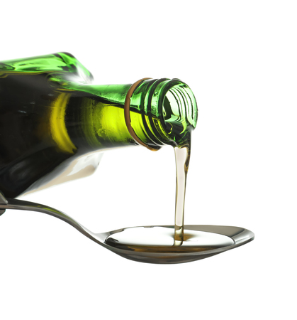 Pouring of olive oil from bottle into spoon on white background 스톡 콘텐츠