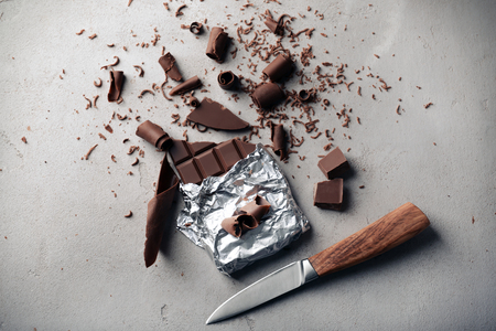 Chocolate bar with curls and knife on grey background