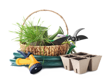 Basket with gardening tools and peat pots on white background