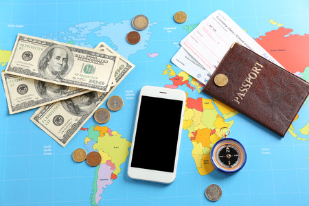 Mobile phone, passport and money on world map. Travel concept