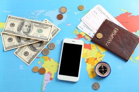 Téléphone portable, passeport et argent sur la carte du monde. Concept de voyage