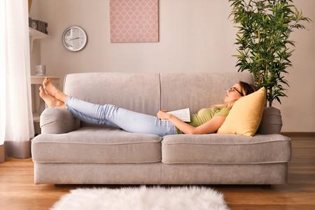 Giovane donna che dorme sul divano con libro Archivio Fotografico