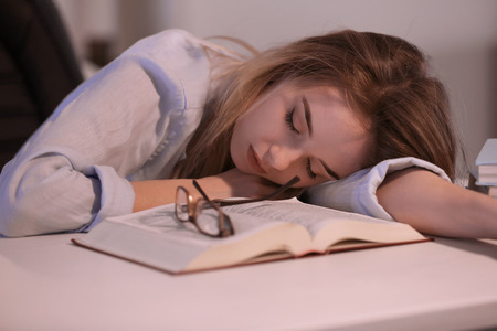 Young woman with book sleeping at table in evening