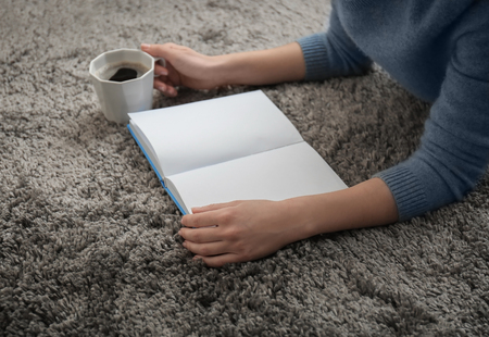 Young woman reading book at home Stock Photo