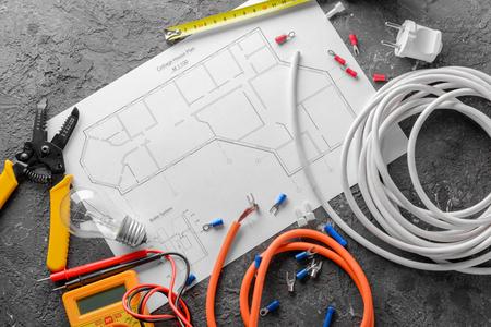 Suministros de electricista con plan de casa sobre fondo gris