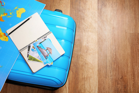Packed suitcase, map and notebook on wooden floor. Travel concept Фото со стока