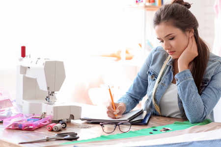 Young female tailor working at table in atelier Stock Photo