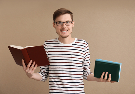 Young man with books on color background Stock Photo