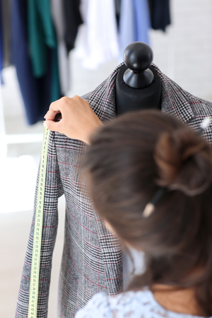 Young female tailor taking measurements of jacket in atelier Stock Photo