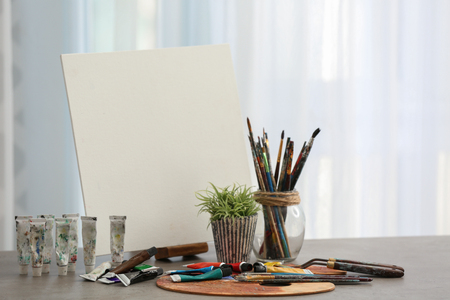 Set of tools and paints with canvas of professional artist on table in workshop