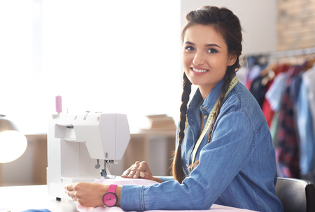 Young female tailor using sewing machine in atelier Stock Photo