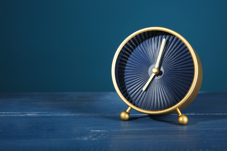 Alarm clock on table against color background. Time management concept
