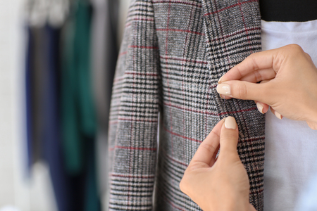 Young female tailor working with jacket in atelier