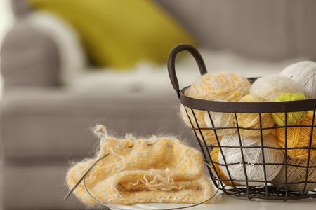 Metal basket with knitting threads on table Banco de Imagens