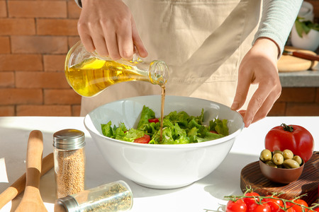 Woman adding olive oil into bowl with fresh vegetable salad on table 스톡 콘텐츠